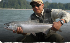 Picture of a man holding a large Coho Salmon, caught on the Kitimat River, British Columbia